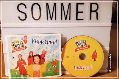 Es steht das Musikalbum vor einer Lightbox auf der mit Buchstaben das Wort Sommer geschrieben steht.