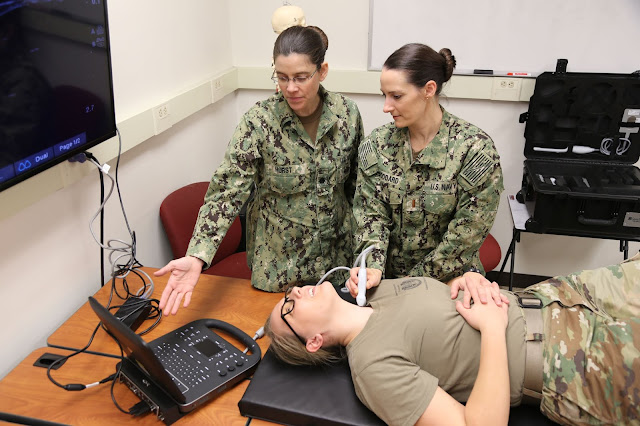 Two students simulate an ultrasound on another student's neck