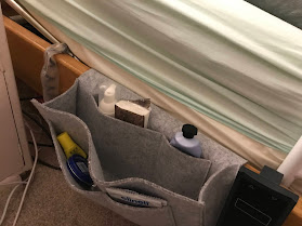 Photograph of a grey pocket organiser tucked under a mattress. Inside some of the pockets are a variety of every day items.