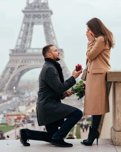 Casal em Paris, o jovem romanticamente ajoelhado oferece uma rosa a jovem.
