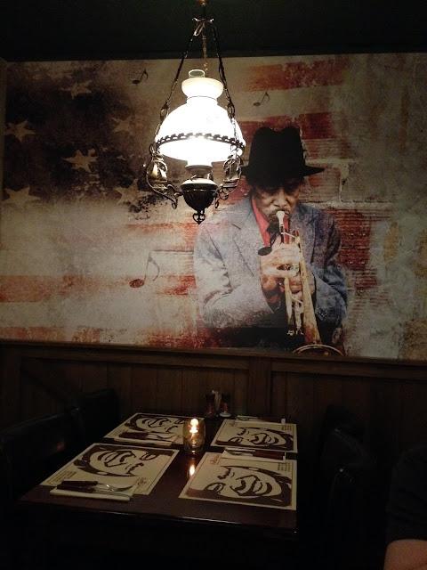 Muiurschildering van een trompettist op de muur bij Fat alice