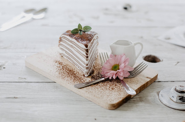 The image showed a layered cake made with crepes. It's a crepe cake on a serving board with flowers, whipped cream and a fork also on the board. The board is sitting on a white wooden table
