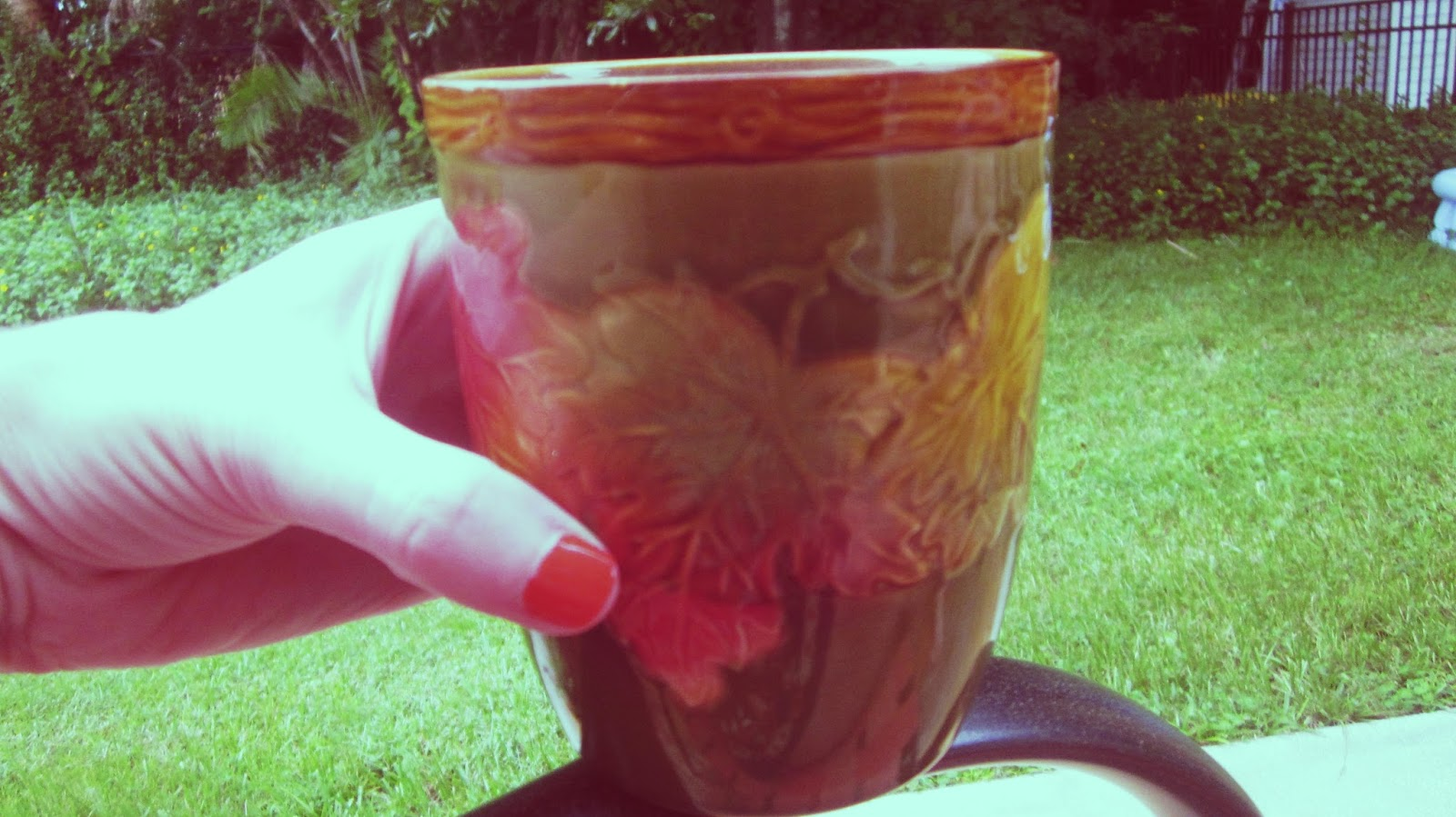 Woman With Red Painted Nails Holding a Woodland Themed Coffee Cup For Relaxing Tea
