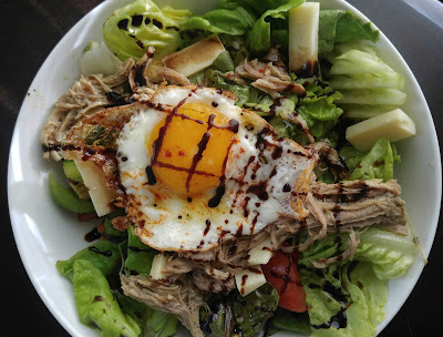 pulled pork in a salad with a sunny heritage egg, cheese topped with balsamic glaze