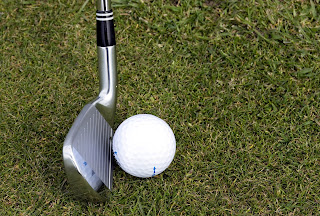 lofted iron and golf ball