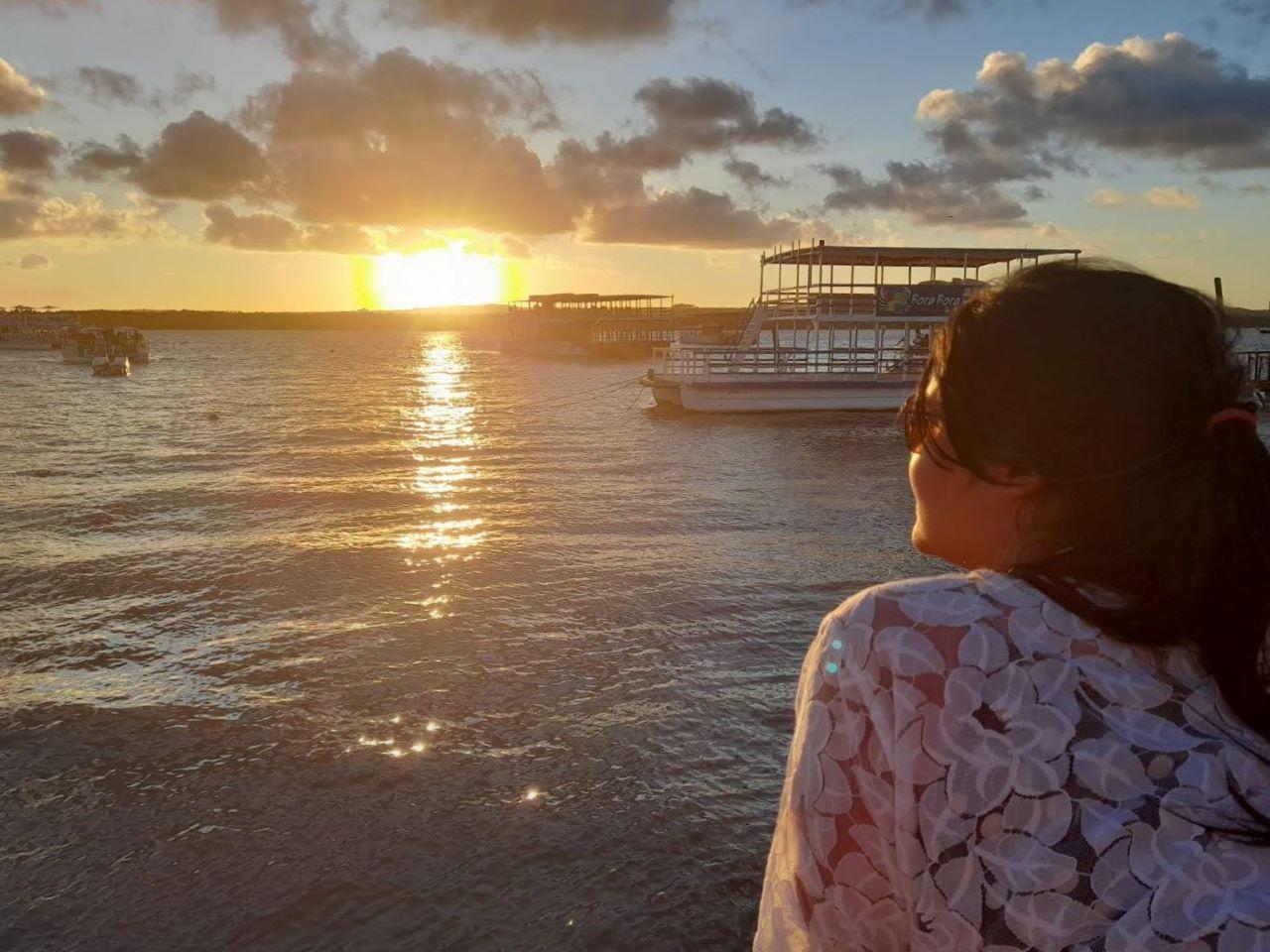mulher de costas vendo o por do sol
