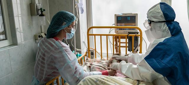 Una joven en una cama de hospital de Ucrania con COVID-19 es atendida por un doctor y su mamá.© UNICEF/Evgeniy Maloletka