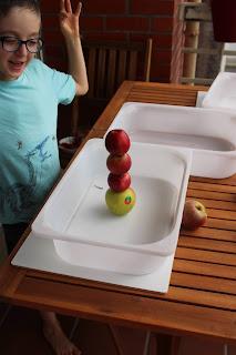 Torre com 4 maçãs empilhadas e criança a comemorar