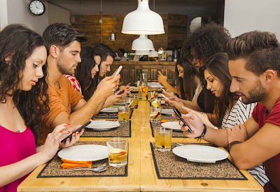 Young people at dinner table not eating or communicating