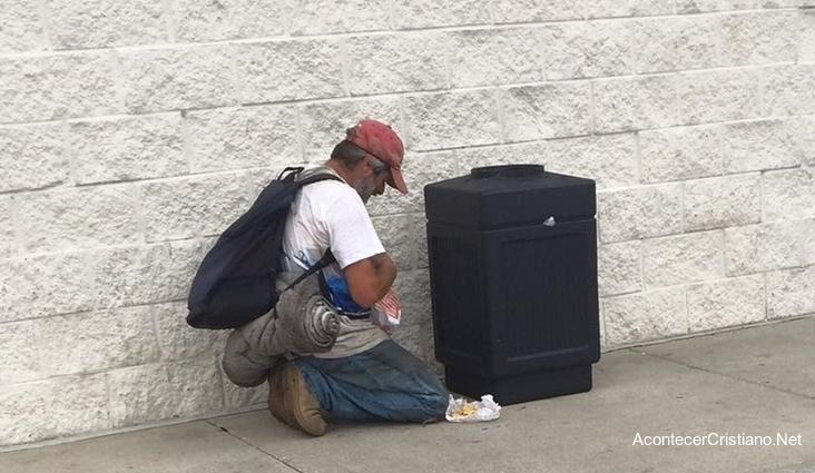 Hombre sin hogar orando por alimentos