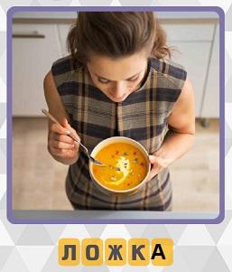 девушка стоя ест суп из чашки с помощью ложки на кухне