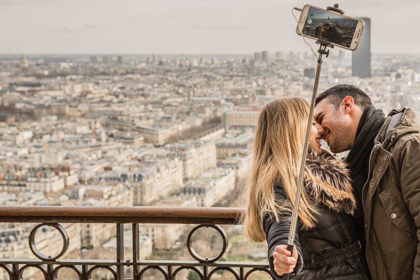 Casal fazendo selfie durante viagem com paisagem ao fundo