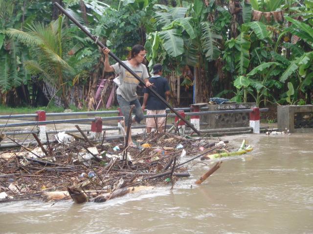 Orang Sedang Membersihkan Sampah di Sungai yang Meluap