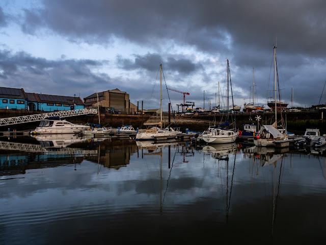 Photo of boats reflected in the still water at Maryport Marina