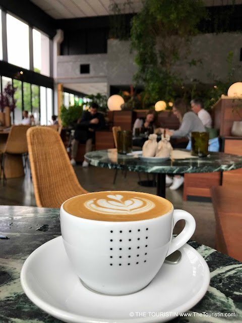 Flat white espresso drink in a white cup with people sitting at tables drinking coffee and chatting