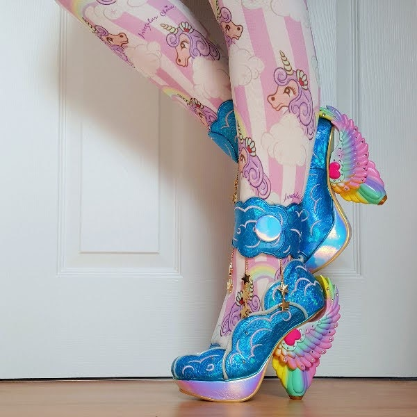 side view of legs with colourful unicorn tights and blue winged shoes