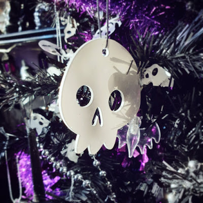 A cartoonish white acrylic skull, very glossy, hanging in the black Christmas tree, with a clear bat-shaped LED string light, silver bead garland, purple tinsel, and black tinsel with white skulls. The shelve and lantern-styled string lights are visible in the background, out of focus, in the upper left