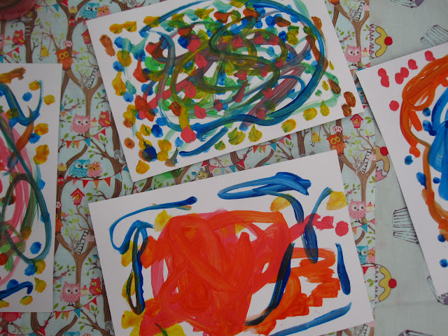 Four squiggly children's paintings being left to try