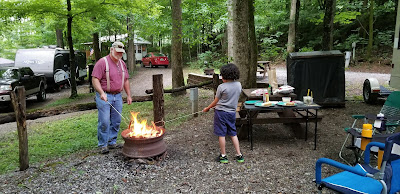 man and boy roasting hot dogs over a campfire