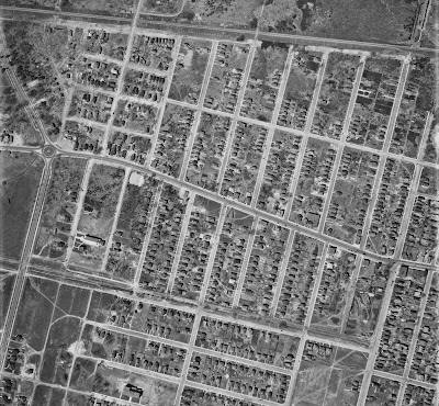 Black and white aerial photo from 1933 showing the west end of Wellington Street with extents Holland Avenue (East), Byron/Tyndall (South), FDC Driveway (Island Park Drive, West) and Scott Street/CPR tracks (North). Also note details including the roundabout at Island Park and Richmond, the streetcar tracks (and streetcar!) on Wellington and Holland and north of Byron, the heavy rail tracks north of Scott Street, and how the City Limits end at Western Ave, two blocks east of Island Park, apparent from the lack of sidewalks and less intense development west of there.
