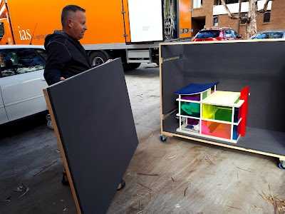 Colourful perspex one twelfth scale modern dolls house in an art packing crate in front of a large truck, with a man holding one side of the crate, ready to put it on.