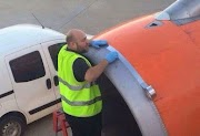 Shocked passenger snaps airport worker using tape on plane engine just moments before take-off