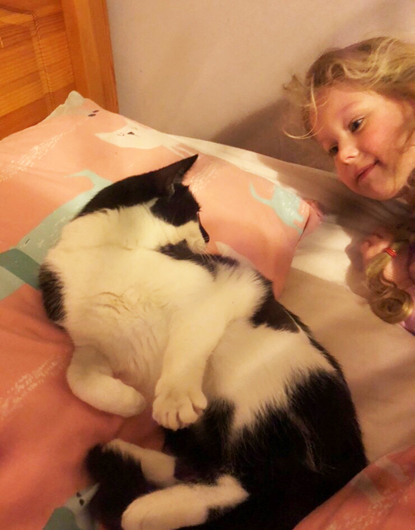 black and white cat lying on bed next to young blonde girl