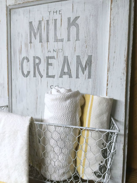 White cabinet door with milk and cream stencil and white basket with towels