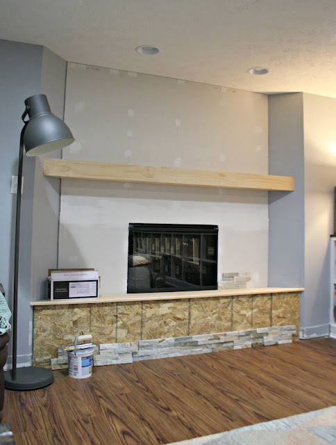 basement fireplace with hearth and mantel