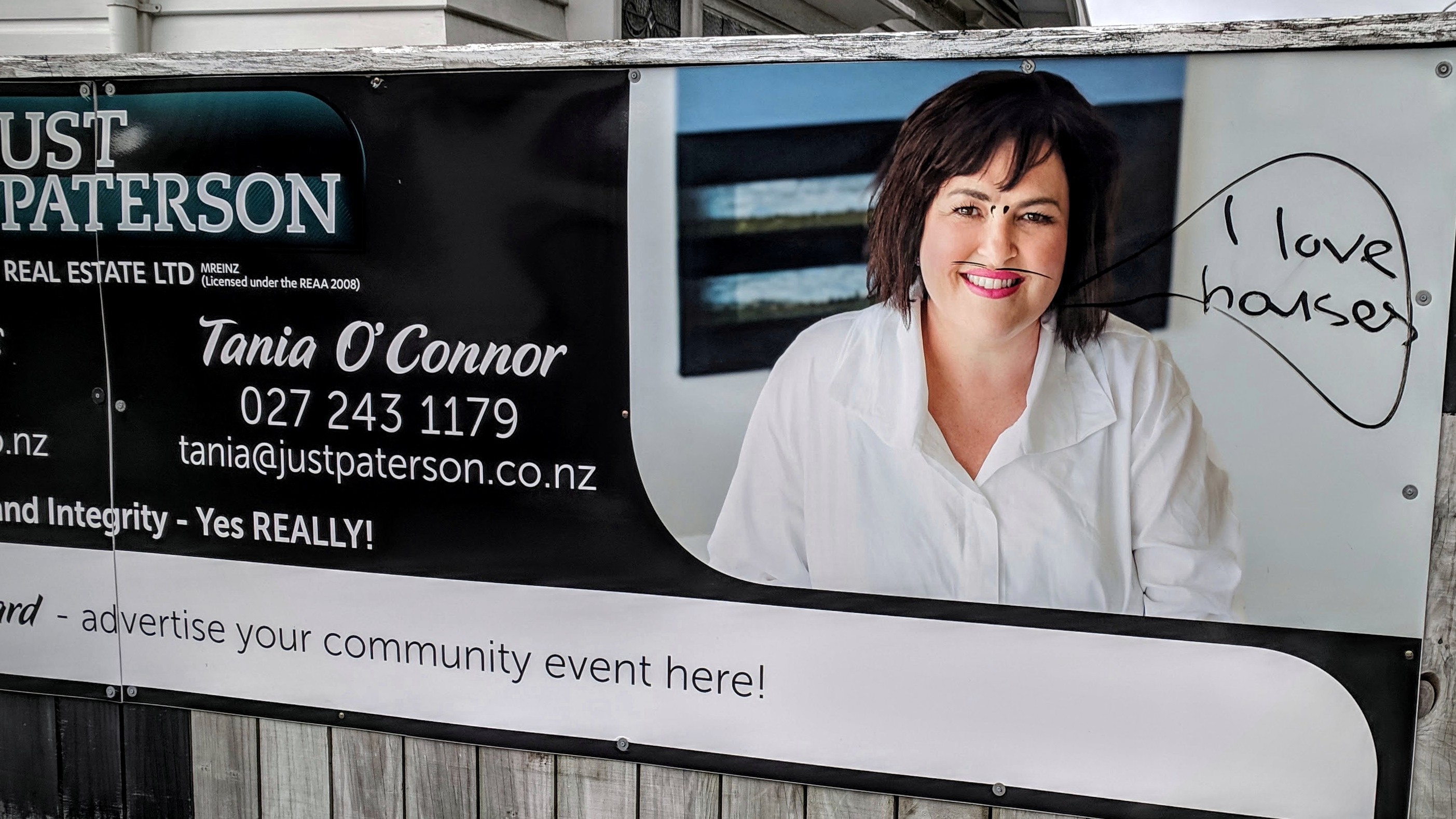 'I love gouses' graffiti on a real estate agent advertising hoarding