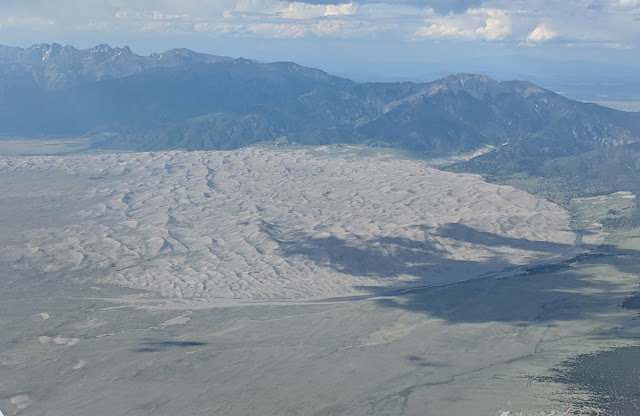 Exposed sand was blown against the Sangre de Cristo mountain range to form these massive dunes. The wide and shallow Medano Creek fronts the dunes.
