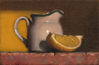Still life oil painting of a small porcelain milk jug beside a lemon quarter.