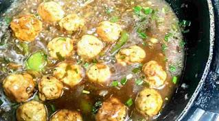 Cooking chicken balls in manchurian gravy in a pan