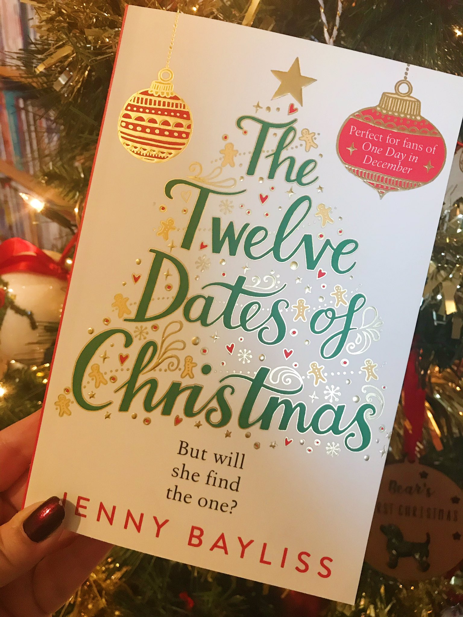The Twelve Dates of Christmas by Jenny Bayliss held up in front of Christmas tree