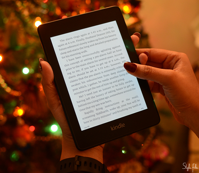 Image of woman's hands with long nails holding a Kindle book reader with bokeh Christmas lights in the background