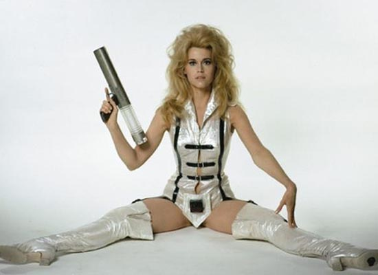 Jane Fonda in white legs spread with gun in Barbarella 1968