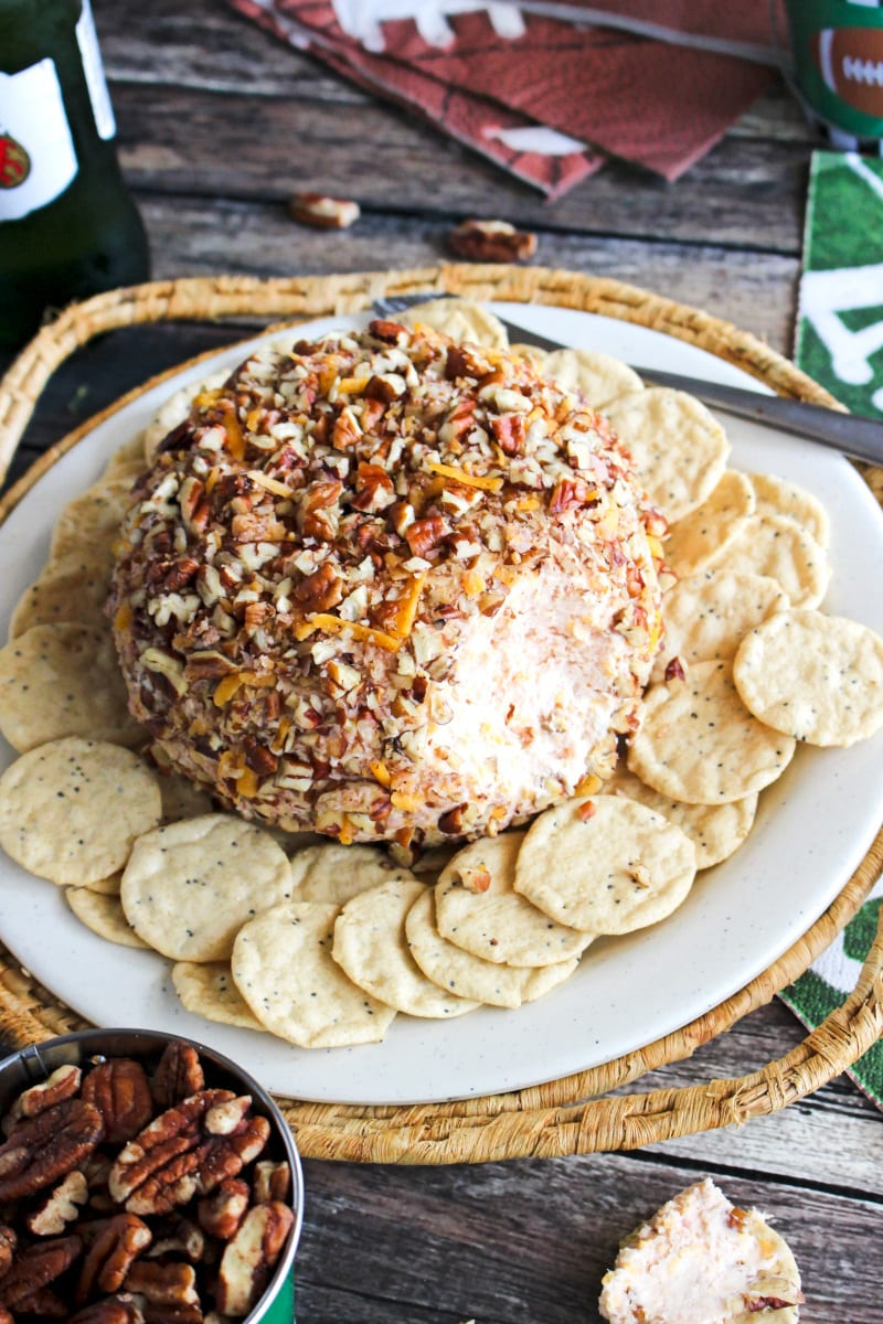 Side angle view of a Ham and Cheddar Cheese Ball on a plate surrounded by crackers on a wood background.