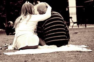 Imagen de una pareja, la chica le toca la cabeza al chico calvo