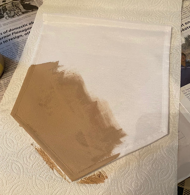Photo of a white banner/flag being painted in putty color.