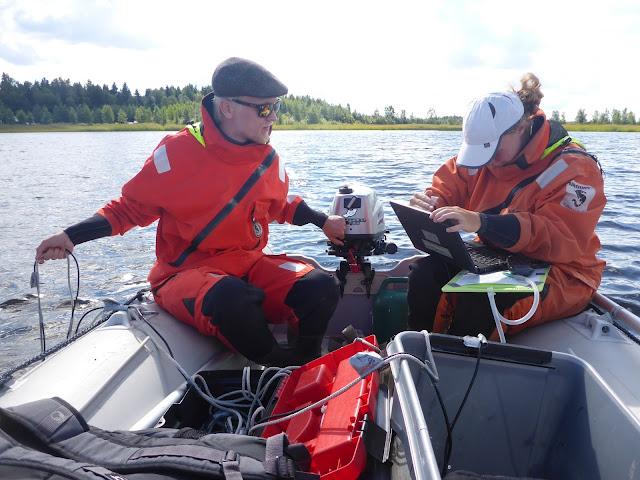 Kaksi henkeä istuu pelastautumispuvuissa kumiveneessä ja videokuvaa veden alle