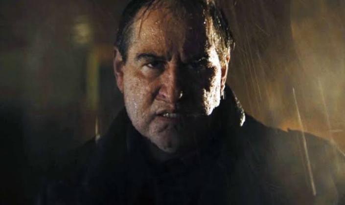 Imagem: cena do trailer de O Batman em que vemos o personagem Pinguim, um homem careca com nariz pontudo e queixo flácido, interpretado por Colin Farrell com prótese, numa chuva a noite.