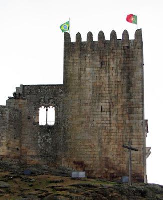 Torre medieval com as bandeiras do Brasil e de Portugal