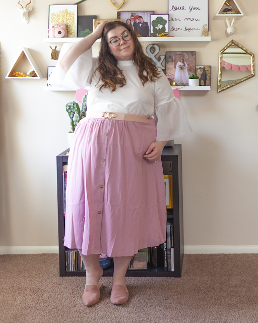 An outfit consisting of a white blouse with sheer sleeves and pink button down midi skirt with pink pointed toe mules.