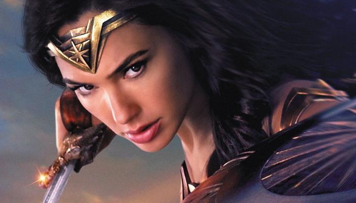Imagem: a Mulher-Maravilha, interpretada por Gal Gadot, uma mulher de cabelos pretos, uma tiara dourada com um símbolo de estrela na testa, usando uma armadura vermelha, com uma espada na mão.