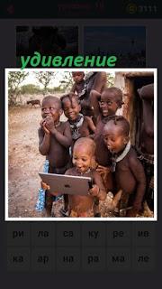 чернокожие дети смотрят в планшет и удивляются