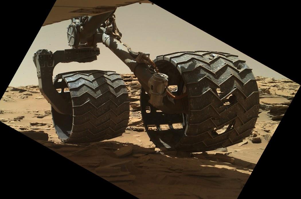 Một năm sau đó, vào ngày 18 tháng 4 năm 2016 nhằm sol 1315, NASA cho sử dụng thiết bị MAHLI để chụp ảnh và kiểm tra lại hiện trạng của hai bánh xe một lần nữa. Hai bánh xe trong hình ảnh này bánh xe bên trái ở giữa và bên trái phía sau. Trên bánh xe xuất hiện những chỗ rách nghiêm trọng vào năm 2013 sau khi tàu tự hành Curiosity băng qua địa hình đá cứng và gồ ghề vào năm 2012, đó là đường đi đã vạch sẵn của nó xuất phát từ địa điểm hạ cánh ở chân núi Sharp. Các nhà khoa học sau đó tiến hành theo dõi chặt chẽ cho đến khi những đường zig zag trên bánh xe bị hư hỏng và gãy vỡ. Các bài thử nghiệm sức bền của các bánh xe trên Trái Đất cũng cho thấy rằng nếu 3 đường zig zag đó bị gãy vỡ, thì bánh xe đó sẽ bị hỏng hoàn toàn, lúc đó nó đã đi được 60% quãng đường theo kế hoạch. Sáu chiếc bánh xe nhám của Curiosity có đường kính 50 cm và bề rộng là 40 cm. Mỗi bánh xe đều được gắn những động cơ riêng cũng như bốn bánh xe ở góc được gắn động cơ dẫn động. Hình ảnh: JPL-Caltech/MSSS/NASA.