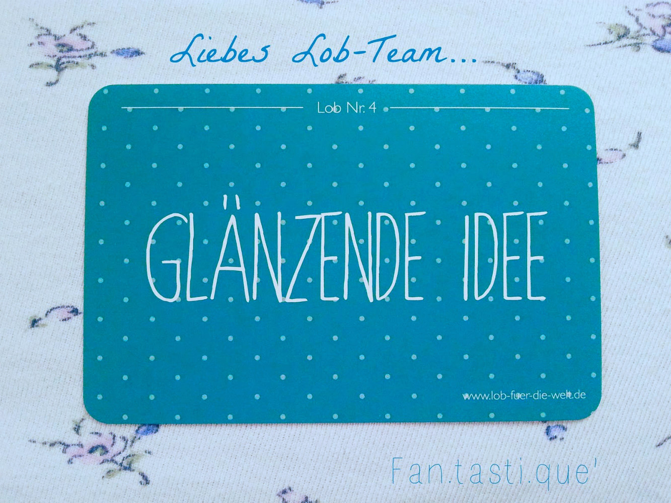 a turquoise Lobkarte saying Glänzende Idee dedicated to the Lob für die Welt team on a floral white piece of fabric