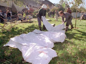 Police carry bodies out of a farm in Cheiry, Switzerland where 23 cultists died in a mass murder-suicide.