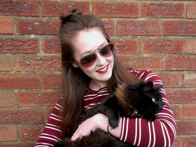 I'm standing in front of a red brick wall, wearing a striped burgundy long sleeve top and sunglasses, and smiling down at the fluffy black cat in my arms