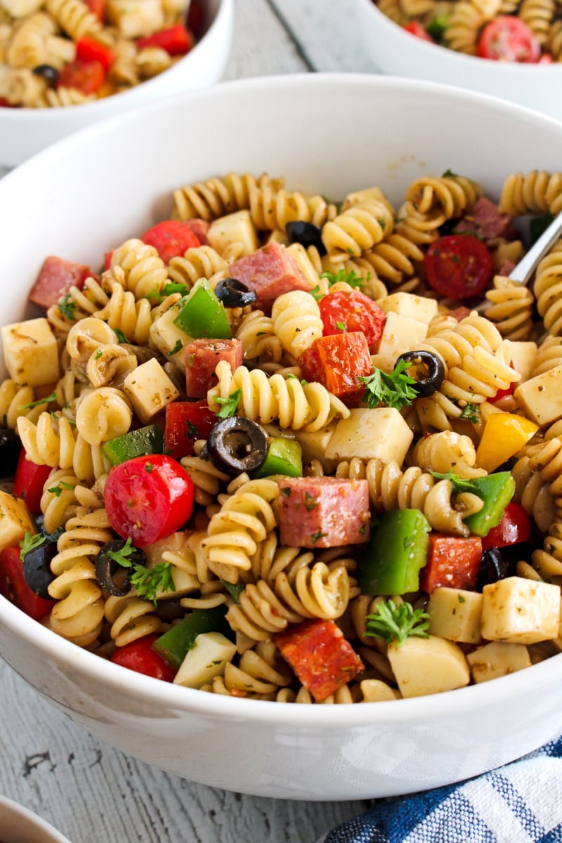 Side view of Manhattan Deli Pasta salad in a white bowl with a blue and white checkered napkin next to it on a white wood background.
